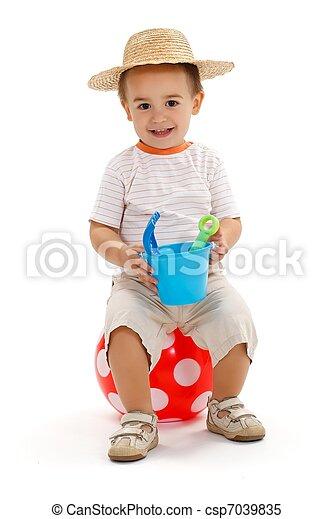 Little boy sitting on dotted ball, holding sandbox toys - csp7039835