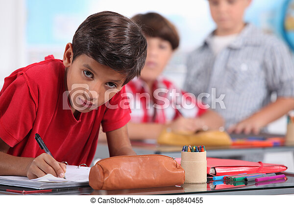 Little boy working in a classroom - csp8840455