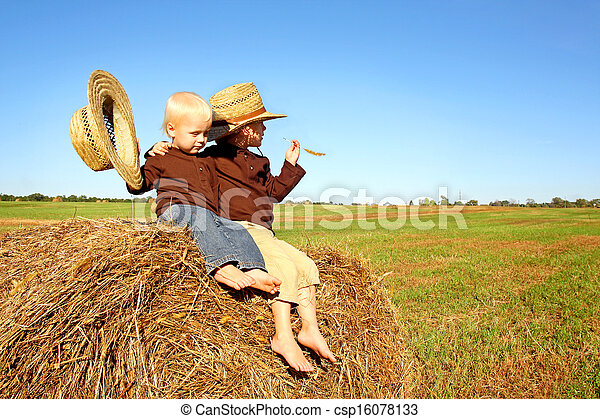 Little Boys Out in the Country on a Hay Bale - csp16078133