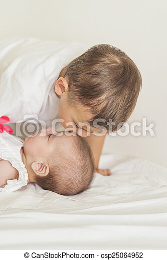 Little Caucasian Boy Kissing His Newborn Sister. Indoors Shot. - csp25064952