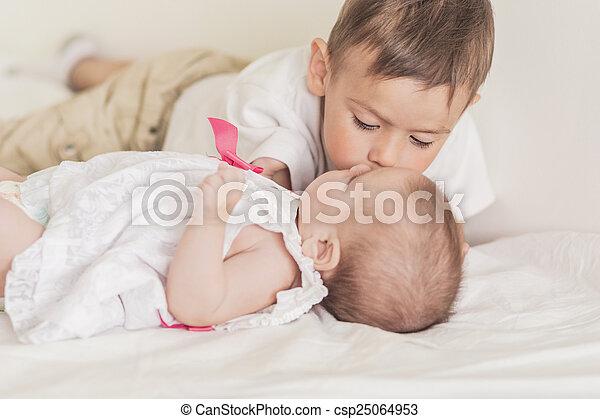 Little Caucasian Boy Kissing His Newborn Sister. Indoors Shot. - csp25064953