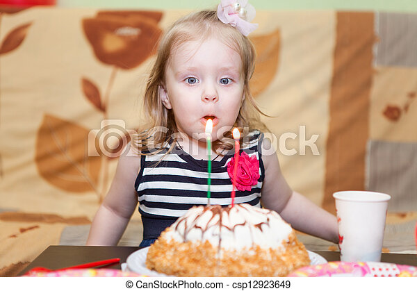 Little Caucasian girl two ears blowing candles on birthday cake - csp12923649