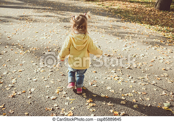 Little child walking on the road with autumn leaves - csp85889845
