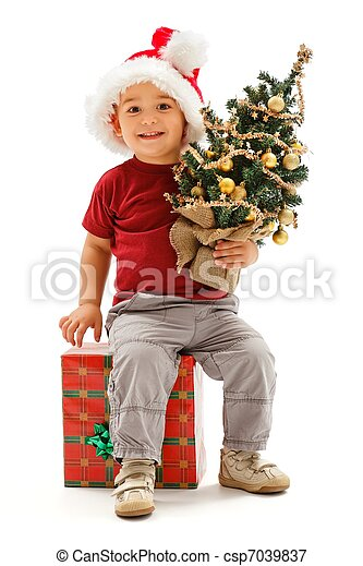 Little christmas boy sitting on present, holding Christmas tree - csp7039837