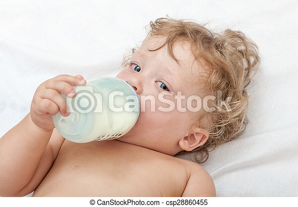 little curly-headed baby sucks a bottle of milk - csp28860455