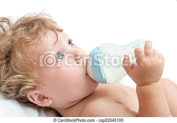 little curly-headed baby sucks a bottle of milk - csp22045100