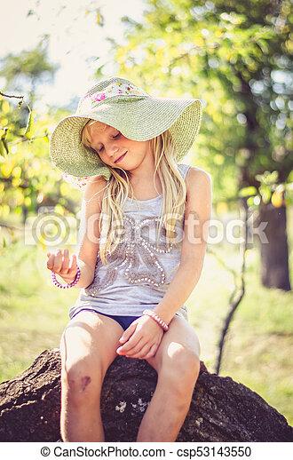little cute blond girl in hat sitting in tree trunk - csp53143550