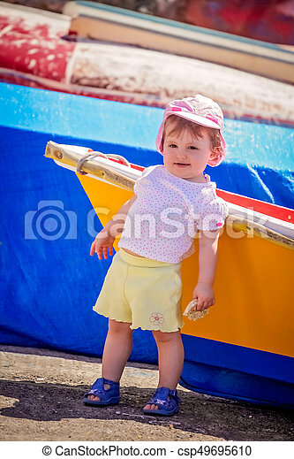 Little cute girl leaning on a colourful wooden boat - csp49695610