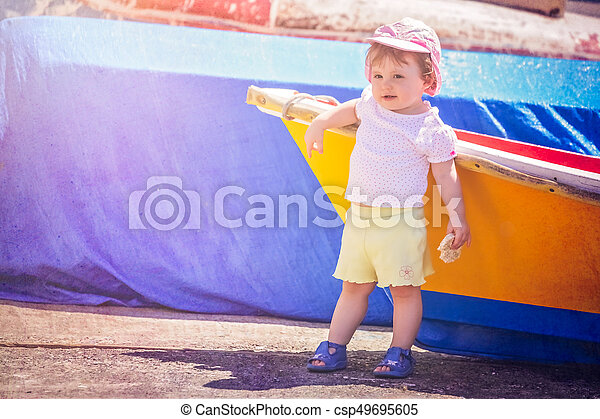 Little cute girl leaning on a colourful wooden boat - csp49695605