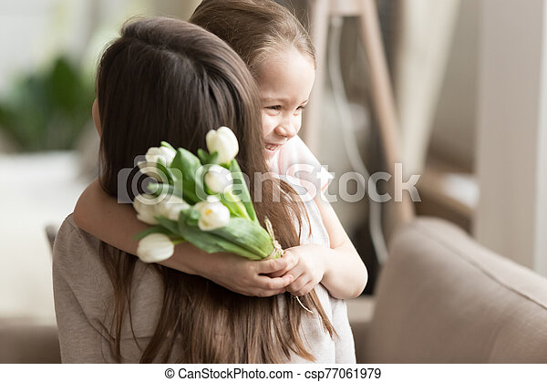 Little daughter hugging, congratulating mother, presenting flowers - csp77061979