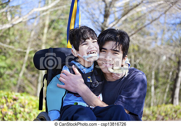 Little disabled boy in wheelchair hugging older brother outdoors, smiling together. Child has cerebral palsy. - csp13816726