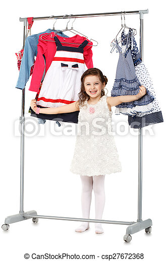Little fashionable girl chooses clothes in a wardrobe - csp27672368