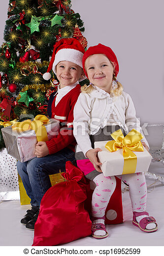 Little girl and boy sitting with gift under Christmas tree - csp16952599