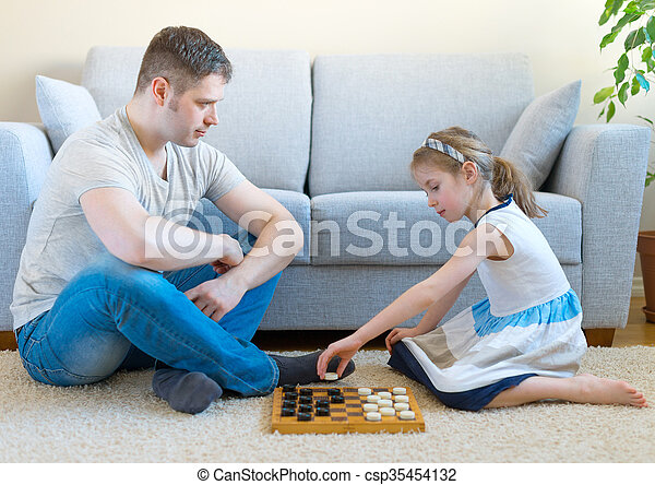 Little girl and her father playing checkers. - csp35454132
