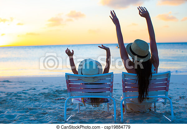 Little girl and mother sitting on beach chairs at sunset picture