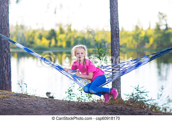 Little girl child in hammock near the lake - csp60918170