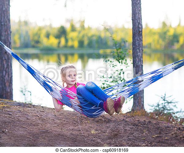 Little girl child in hammock near the lake - csp60918169