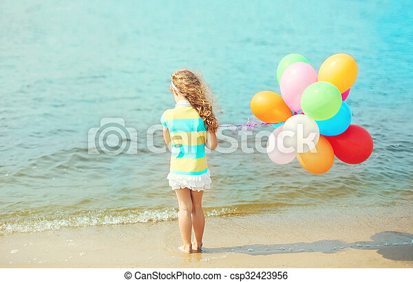 Little girl child with balloons standing on beach near sea, view back - csp32423956