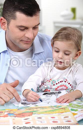 little girl colouring under dad's watchful eye - csp8894808