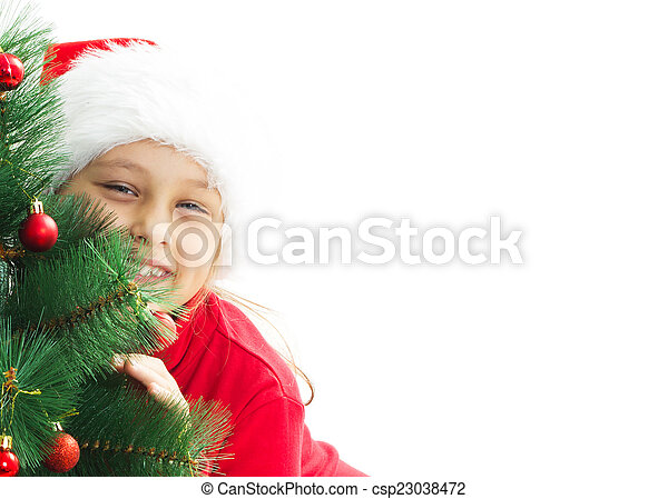 little girl dressed as Santa hugging a decorated Christmas tree - csp23038472