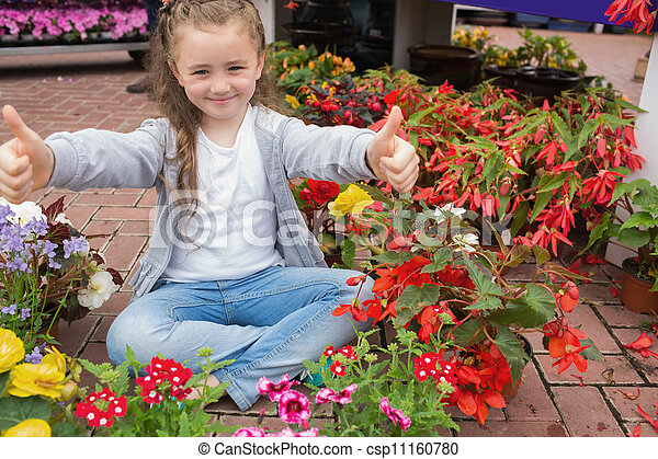 Little girl giving thumbs up while sitting on the floor - csp11160780