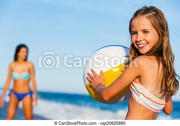Little girl holding beach ball with mother in background. - csp30625890