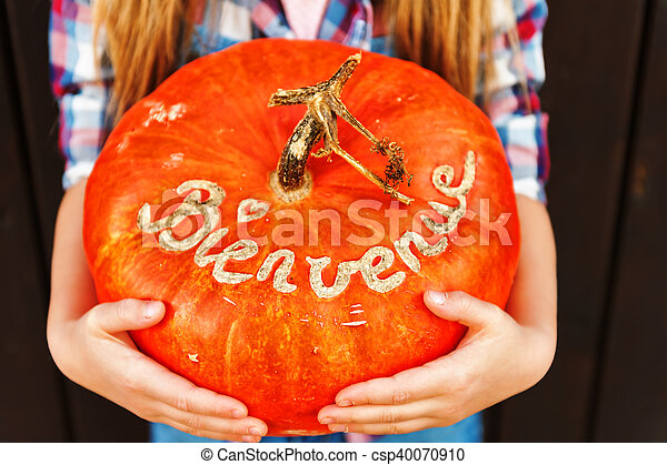 Little girl holding big pumpkin with french sign Bienvenue (welcome) - csp40070910