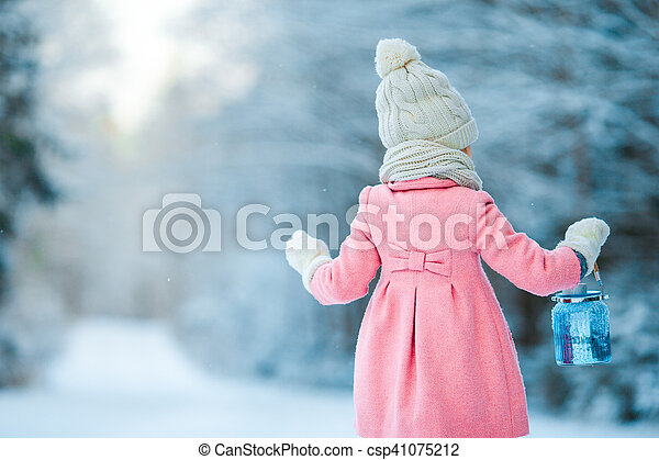 Little girl holding Christmas lantern outdoors on beautiful winter snow day - csp41075212