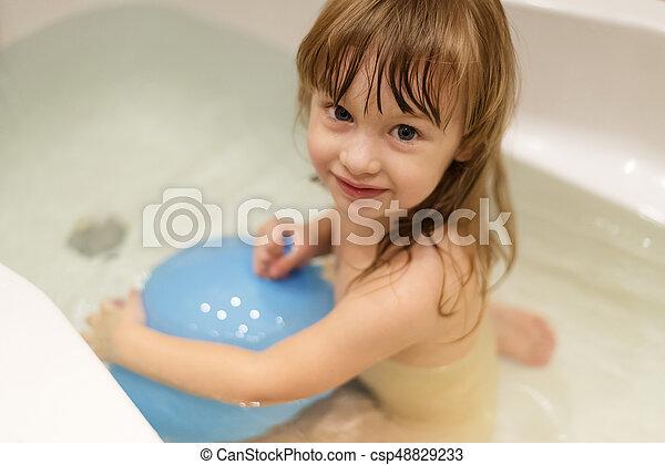 little girl in a bathroom little girl sitting in a bath with a blue