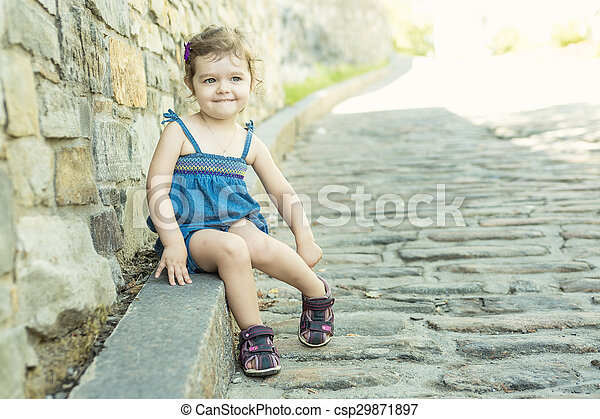 Little girl in an urban setting smiles at the camera. - csp29871897