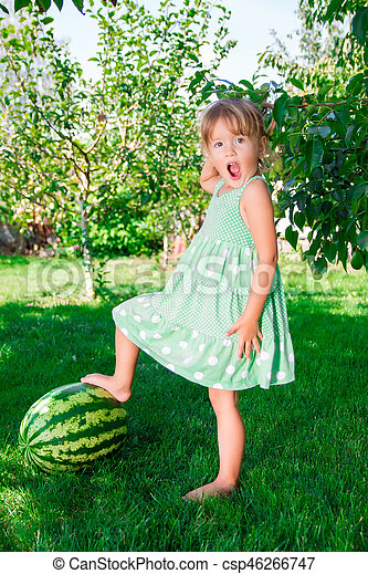 348191a5253c Little girl in green dress barefoot standing on watermelon in the park.  Summer time.