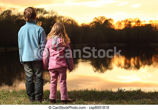 Little girl in pink clothes and boy in blue jacket holding hands and standing back on bank of river and admire on sunset - csp8001818