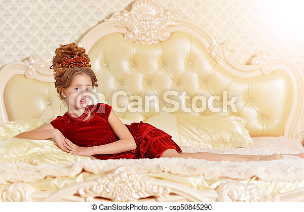 116021a4b3b4 Cute little girl in red velvet dress with retro hairstyle lying on ...