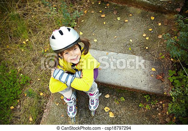 Little girl in roller skates at a park - csp18797294