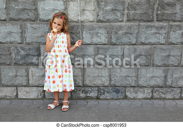 Little girl in white sarafan eats an ice-cream and holds an air marble near stone wall - csp8001953