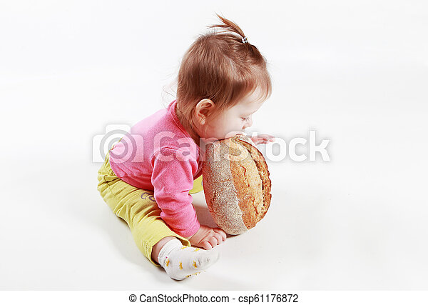 little girl is played with bread in the studio on a white background - csp61176872