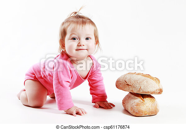 little girl is played with bread in the studio on a white background - csp61176874