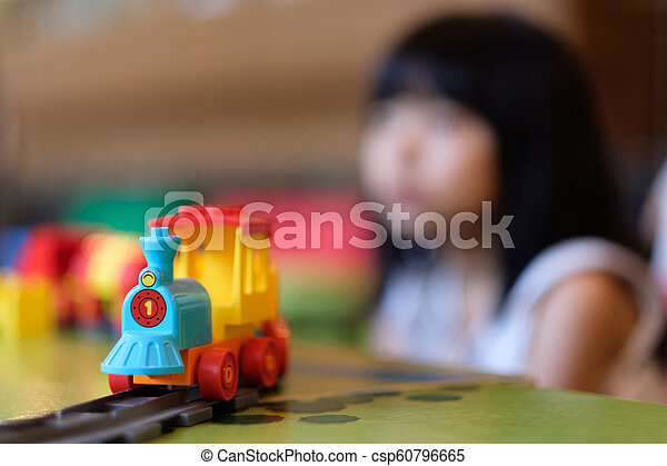 Little girl kid playing with train toy - csp60796665