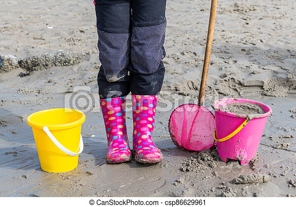 Little girl on a beach with 2 buckets and a net - csp86629961