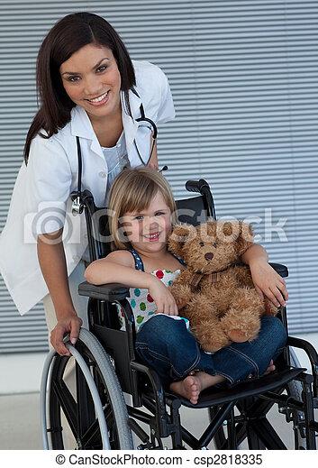 Little girl on a wheelchair holding her teddy bear - csp2818335