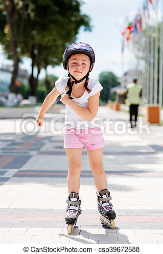 Little girl on roller skates in helmet at a park - csp39672588