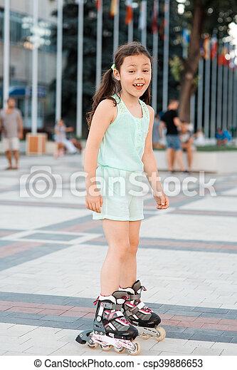 Little girl on roller skates in helmet at a park - csp39886653