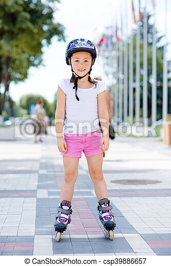 Little girl on roller skates in helmet at a park - csp39886657