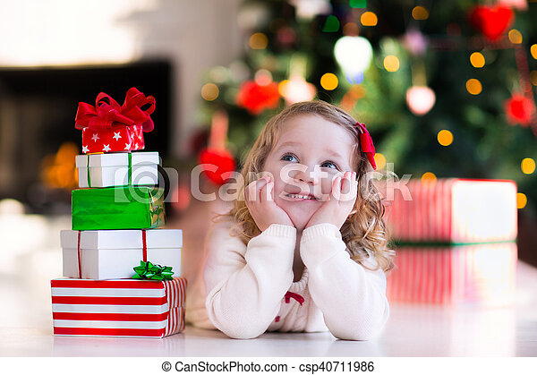 little girl opening presents on christmas morning csp40711986