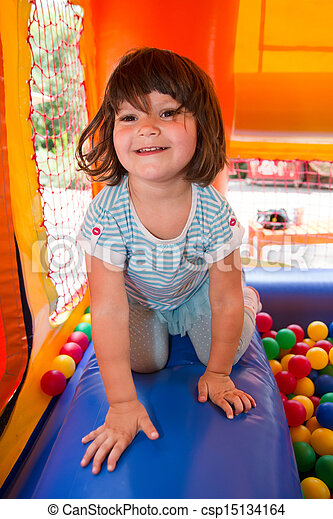 Little girl playing in inflatable bouncing castle - csp15134164