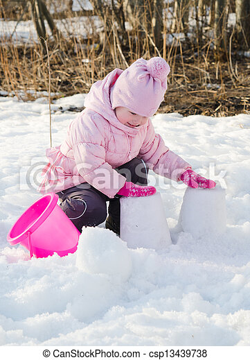 Little girl playing in the winter with snow  - csp13439738