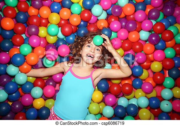 little girl playing lying in colorful balls park playground - csp6086719