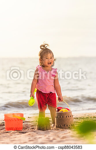 little girl playing sand with toy sand tools - csp88043583