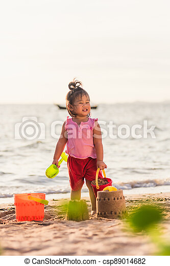 little girl playing sand with toy sand tools - csp89014682