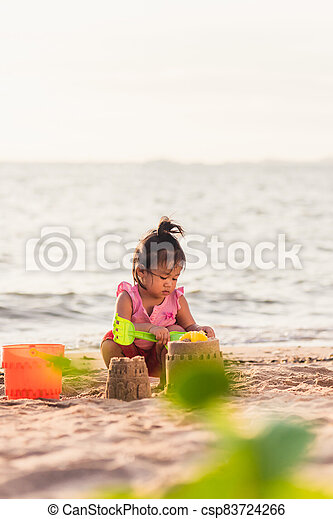 little girl playing sand with toy sand tools - csp83724266